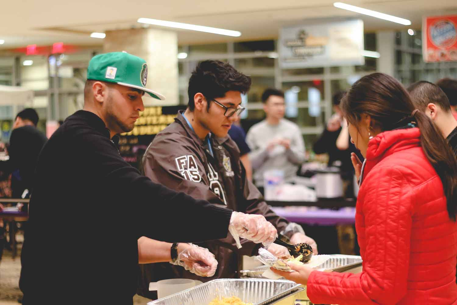 Members of Lambda Theta Pi, a Latin fraternity on campus, serve traditional dishes to attendees. Photo by Hanna Yowell.