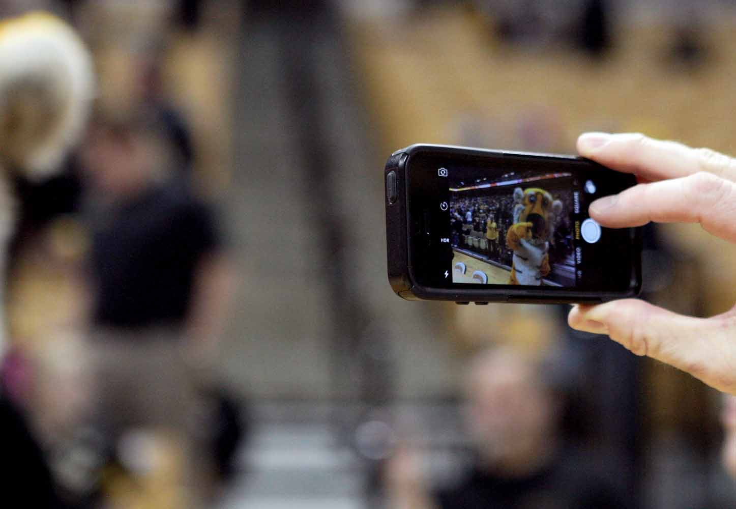 A member of the media snaps a photo of Truman the Tiger on his iPhone to post to social media before the game against Alabama Thursday evening, Feb. 11, 2016.