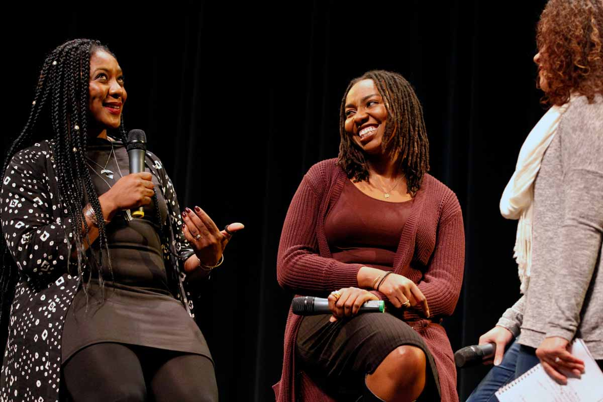 """Alicia Garza, left, a co-founder of the Black Lives matter movement, laughs with Opal Tometi at the beginning of the panel discussion Thursday evening, Feb. 18, 2016. """"Maybe we can get rid of the binaries o right and wrong and focus on what'll set up free,"""" Garza said. Photo by Tanzi Propst."""