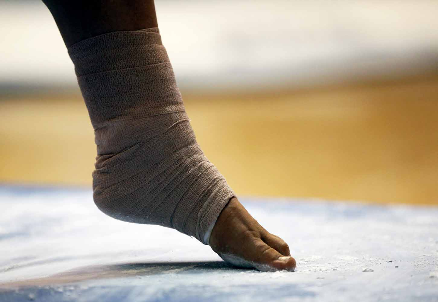 Mizzou sophomore Shauna Miller rubs her toes and the balls of her feet in chalk dust on the mat near the balance beam before her performance Friday evening, Feb. 19, 2016 in the Hearnes Center.