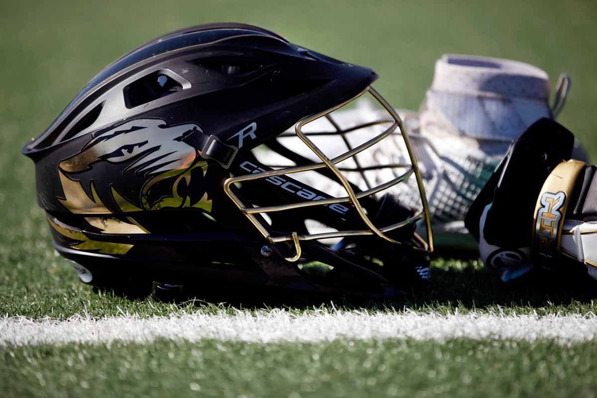 A Mizzou men's lacrosse helmet and gloves are discarded on the sideline of Stankowski Field Sunday morning, Feb. 21, 2016 during the game against Oklahoma State University.