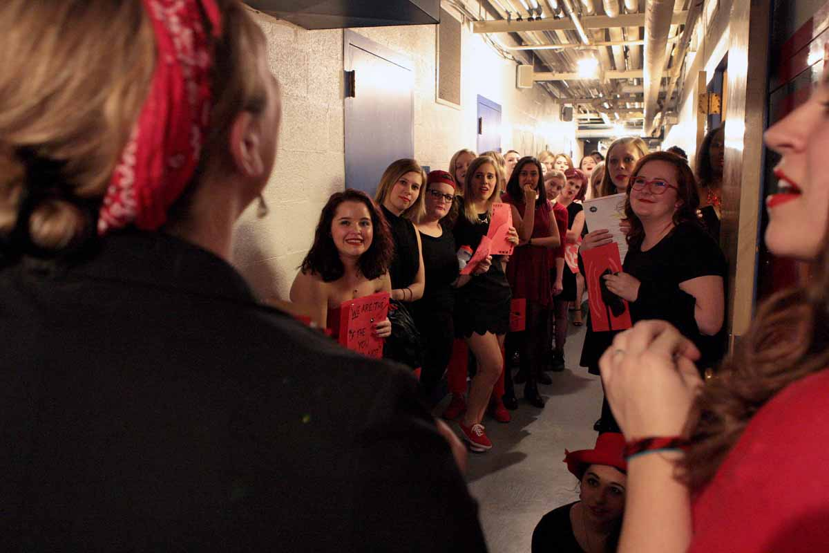 Kelsey Burns, one of three advisors for the Vagina Monologues, pep talks the actresses in the hallway below Jesse Auditorium's stage Saturday evening, Feb. 27, 2016 before the show.