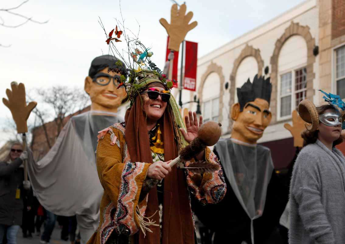 A parade attendee marches in front of caricatures of True False co-founders Paul Sturtz and David Wilson on Walnut Street. Photo by Tanzi Propst.