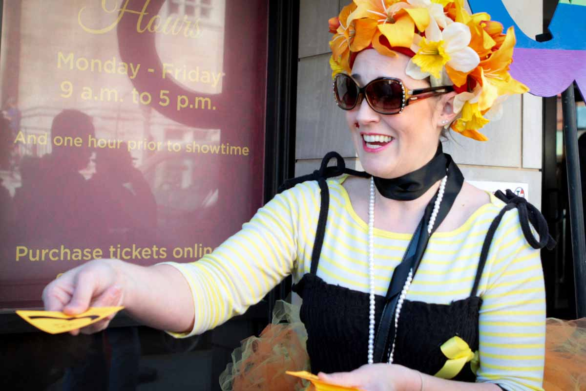 Volunteer Beth Hunter passes out Q cards outside of the Missouri Theatre for the 4 p.m. showing of Starless Dreams Saturday afternoon. Photo by Tanzi Propst.