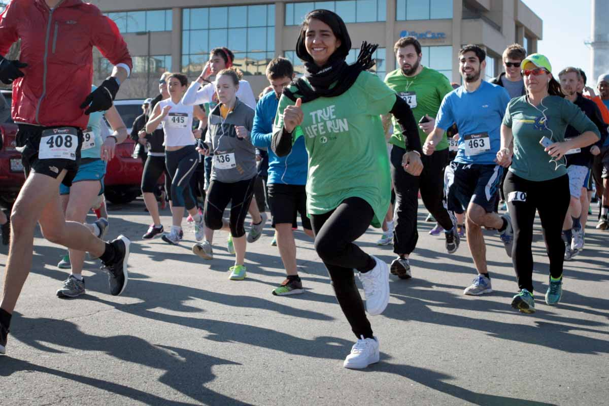 True Life 5K runners take off from Flat Branch Park Saturday morning. Sonita Alizadeh, originally from Afghanistan and the subject of 'Sonita,' leads the pack. The race includes four different obstacles — running stairs, hopscotch, red light/green light and an egg race. Photo by Tanzi Propst.