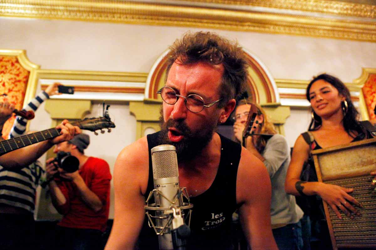 Romain Smagghe of Les Trois Coups raps in French into the microphone during Busker's Last Stand in the main area of the Missouri Theatre Sunday evening after the final movie ends. Photo by Tanzi Propst.