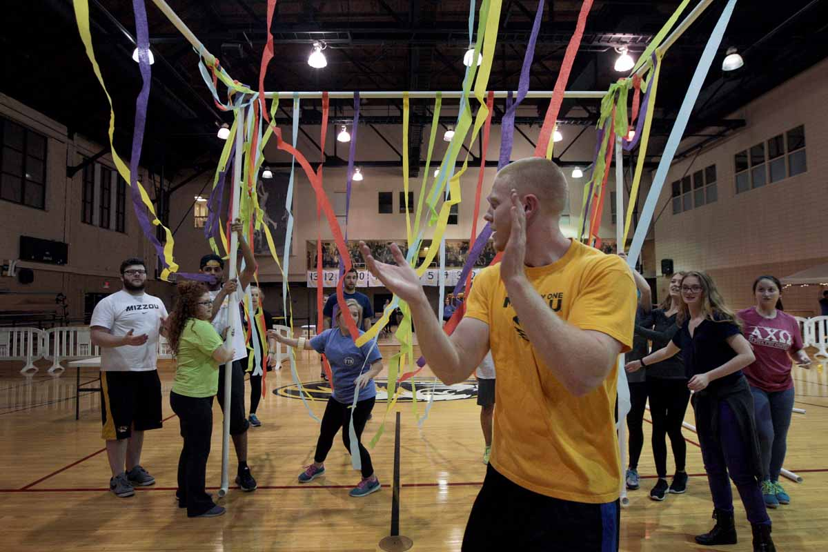 Senior Carson Miller, vice president of recruitment for MizzouThon, applauds as other leadership members help to erect the jail station after attaching streamers for decoration Friday evening.