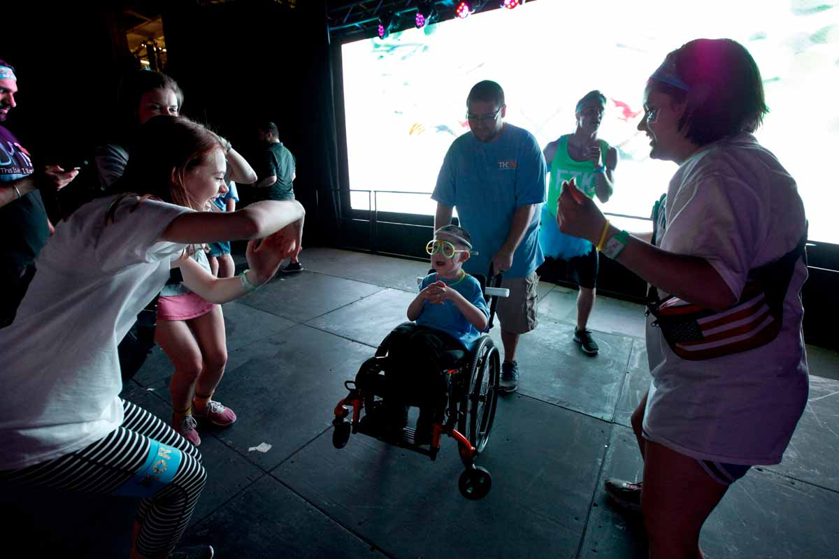 Declan Johnson, 8, dances with his dad and MizzouThon leadership members Leah Hoelscher and Ann Marie Metzendorf on stage near the end of Power Hour.