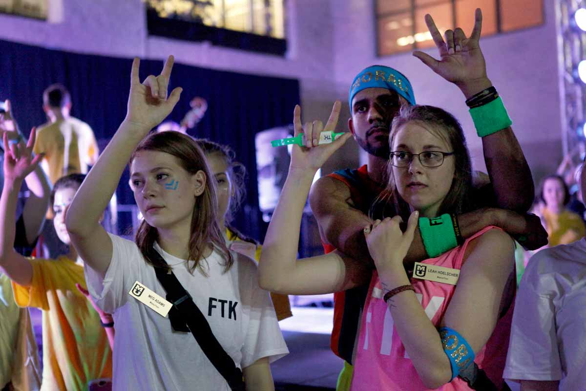 "Meg Adams and Leah Hoelscher raise their hands in the air with the rest of MizzouThon leadership and dancers forming the sign language for ""I love you"" as Miracle Families cut wristbands off each dancer at the conclusion of the main event."