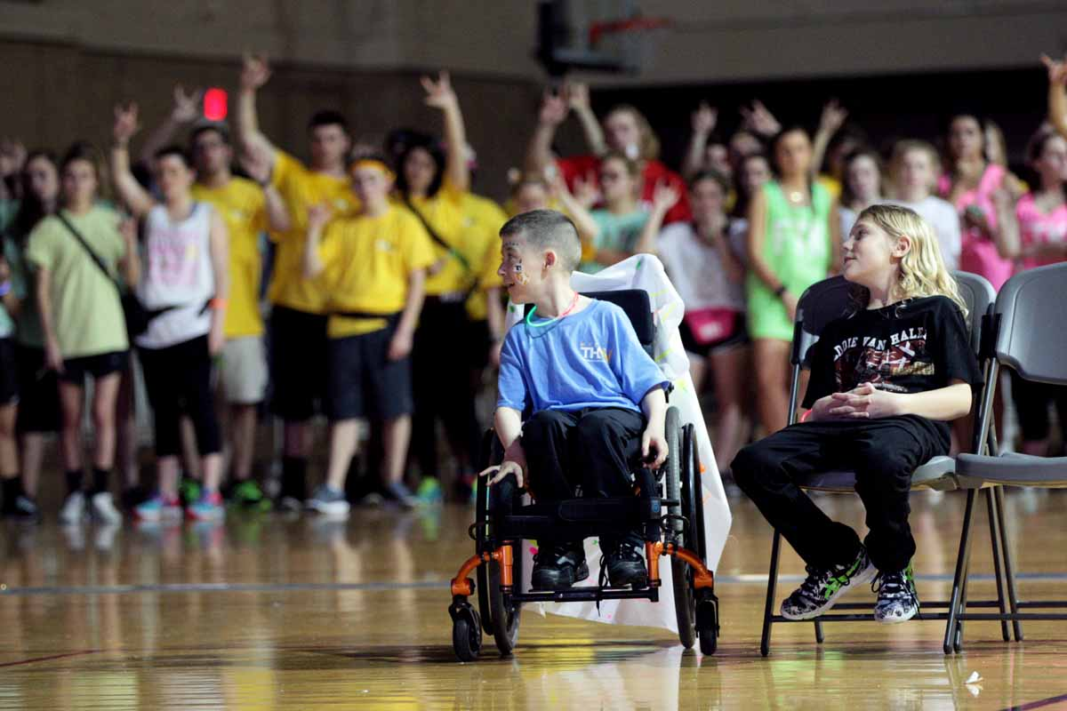 From left, Declan Johnson, 8, and Beau Edwards, 10, sit in the middle of a ring of dancers that just finished dancing 13.1 hours for them and other children like them.