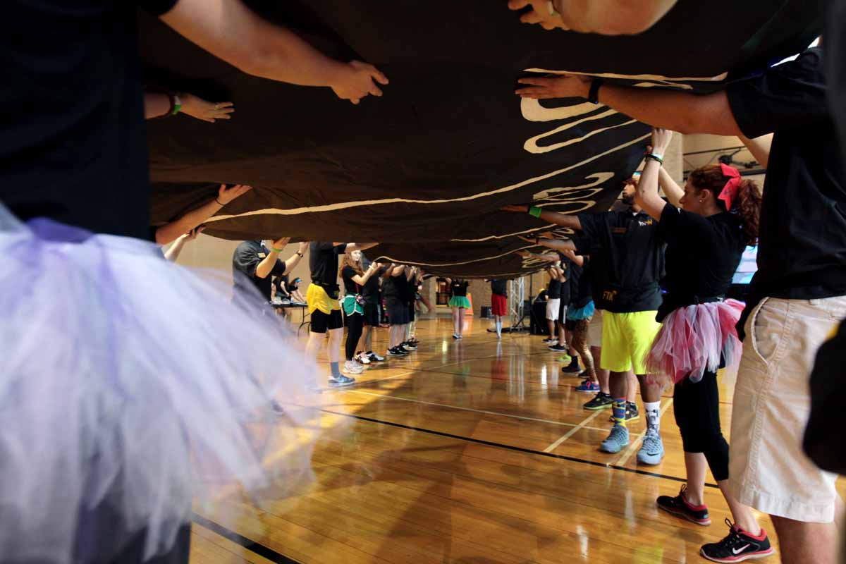 MizzouThon leadership members carefully carry a banner across the gym at the Mizzou Rec Center and over to a wall during set up Saturday morning, March 12, 2016. The banner allowed dancers to place a paper balloon under the amount of money they had raised.