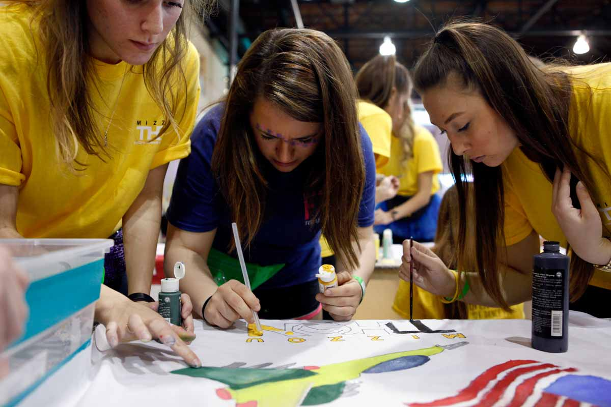 "From left, Emmi Apel, Kylie Alexander and Caitlyn Guy work on Miracle Child T.J. Clime's banner, taking a break from dancing. Apel, a senior, expressed how bummed she was that she wasn't able to participate last year. ""I put everything into it this year,"" she said."