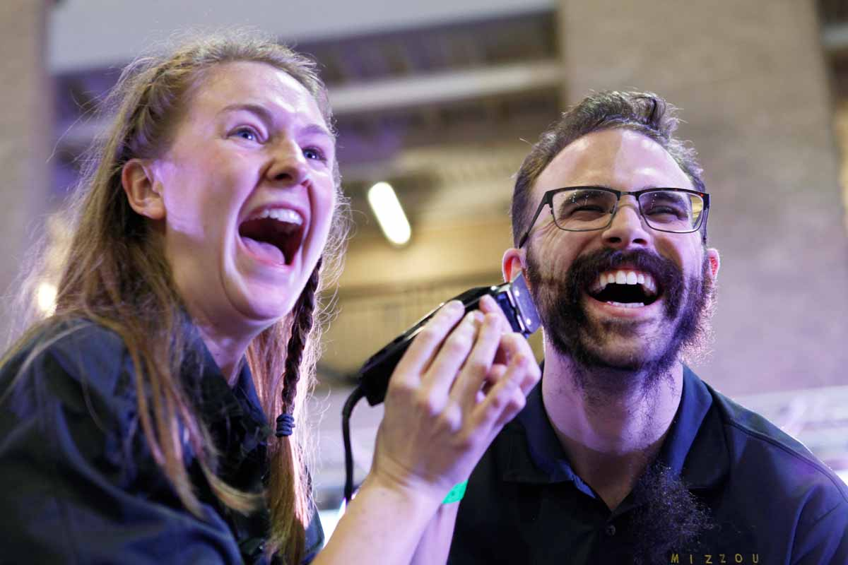 Senior Erin Ehlers, shaves her boyfriend Aaron Warning's beard during the main event Saturday, March 12, 2016. Warning had spent 10 months growing out his beard, claiming that if he raised over his $1,000 fundraising goal he would shave it off for the kids.