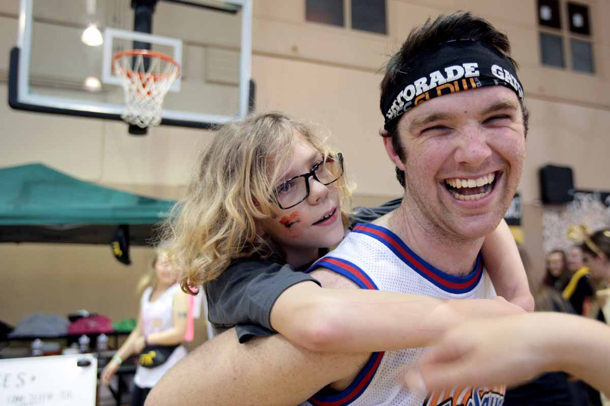 Sean Miller laughs as he carries Miracle Child Bryce Edwards, 10, on his back during the main event Saturday, March 12, 2016. Edwards was born as a micropremie with his twin Beau and after a sever brain bleed, Bryce developed cerebral palsy.
