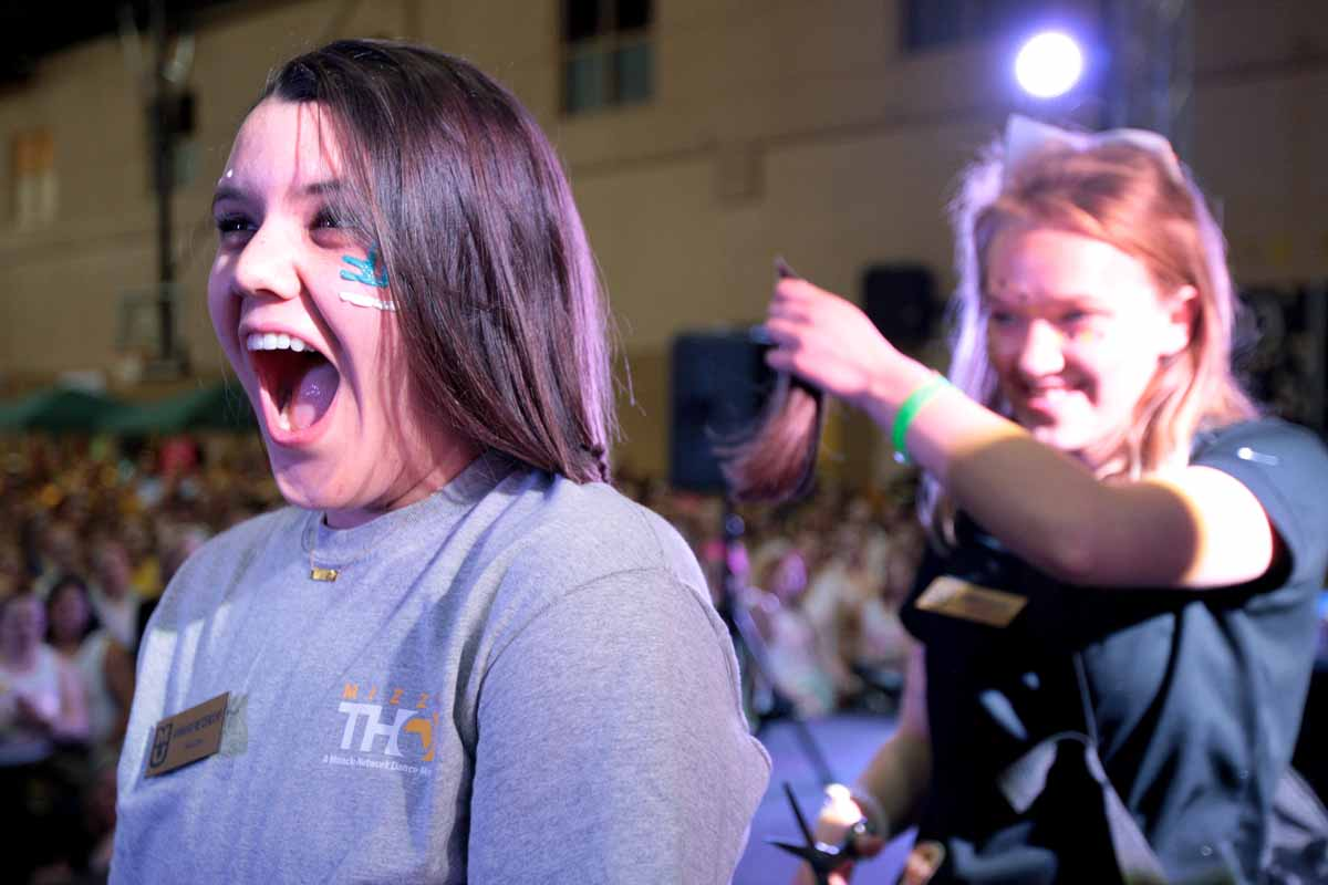 Sophomore Ann Marie Metzendorf, internal recruitment leadership member and morale captain, has her hair cut by Sarah Godke during the main event Saturday evening.