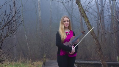 Eimear Arkins holding a viola and standing in the fog.