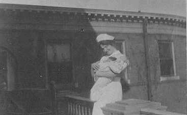 Ada Belle Cowden in a nursing uniform, holding a baby.