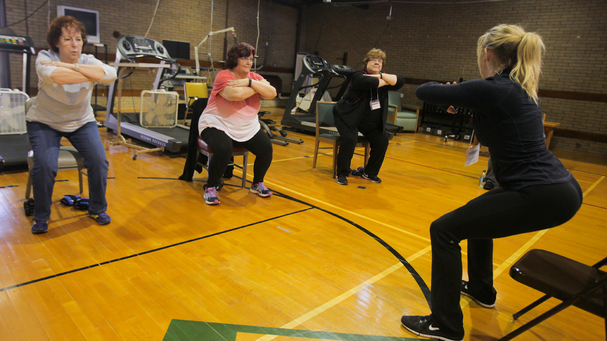 People in chair pose in a gym.