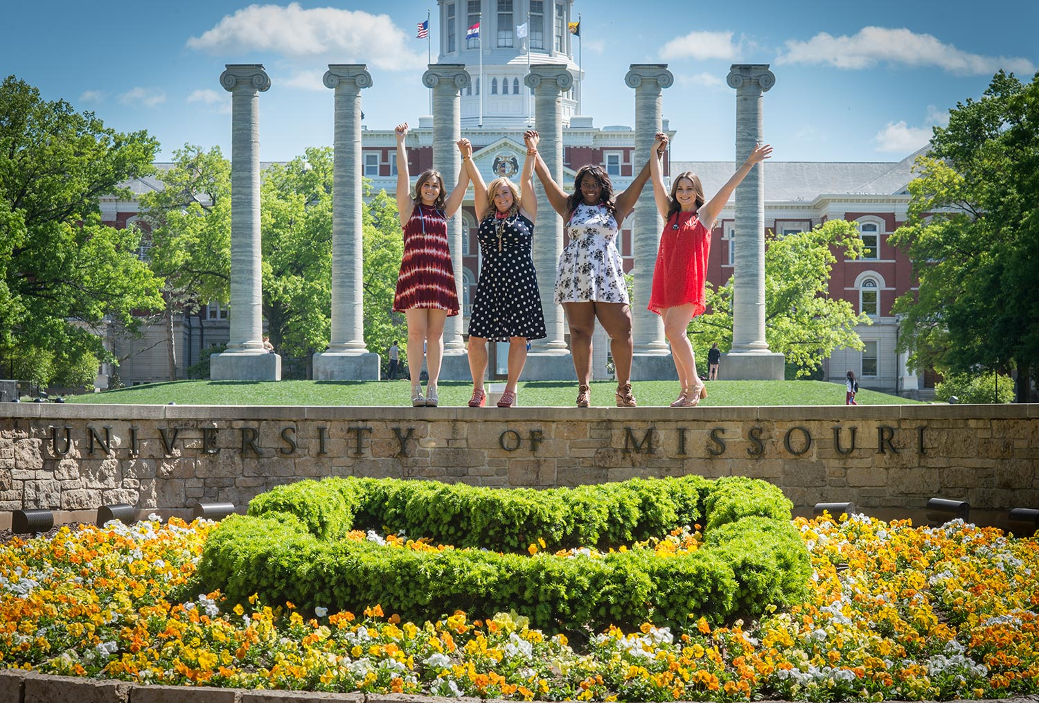 Nursing majors Shannon Williams, Rachel Starkey, Christyl Thurman and Haley Neff reach for the sky where Eighth Street intersects with the heart of campus.