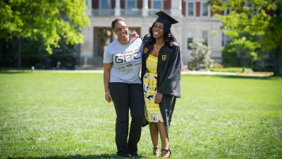 Communication major Andrea Boyd and secondary education major Tiara Williams pose for a portrait on The Quad. Williams is a first-generation college graduate who plans to teach English in her home town of Kansas City. Both young women are Alpha Kappa Alpha sisters who will be graduating next week.