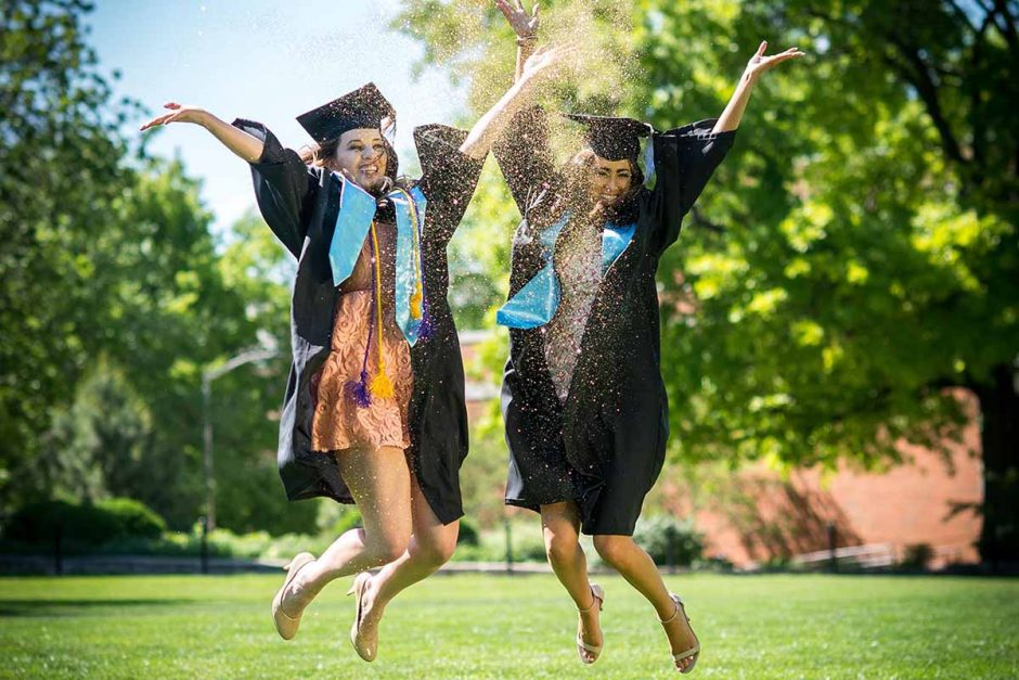 Marketing major Vanessa Salomon and communication major Holly Sias celebrate their impending graduation by jumping for joy with gold glitter. Photo by Shane Epping.