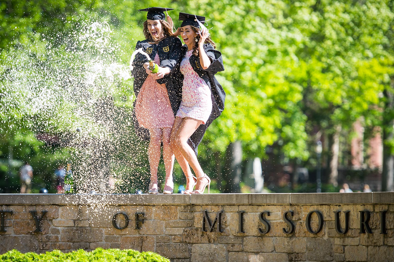 Marketing major Vanessa Salomon and mass media communication major Holly Sias celebrate their pending graduation with a bottle of sparkling bubbly.