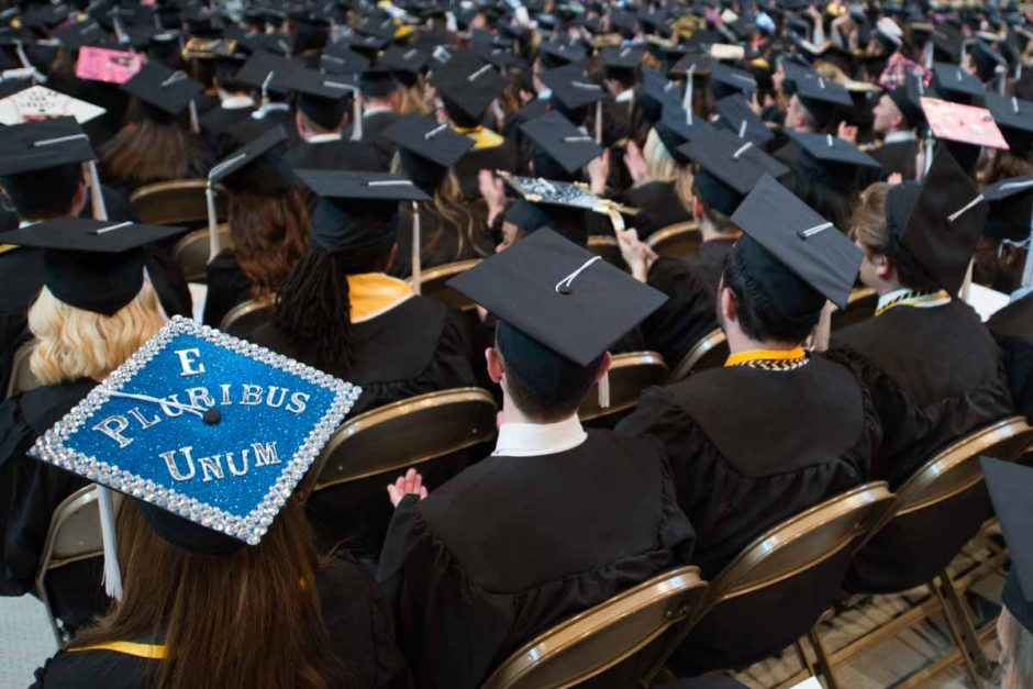 """E pluribus unum, Latin for """"Out of many, one"""" is a phrase on the Seal of the United States and this graduate's mortarboard. Photo by Shane Epping."""