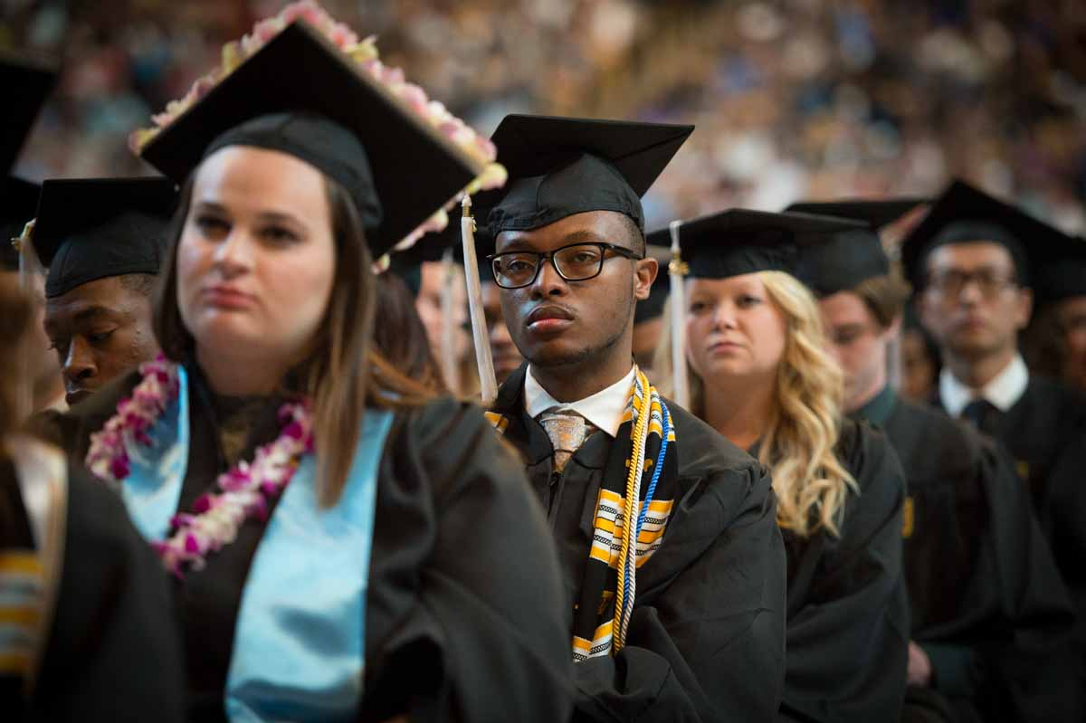 4431474b2e0 David Wallace (center) and classmates listen to a speaker at the College of  Arts   Science ceremony. Photo by Shane Epping.