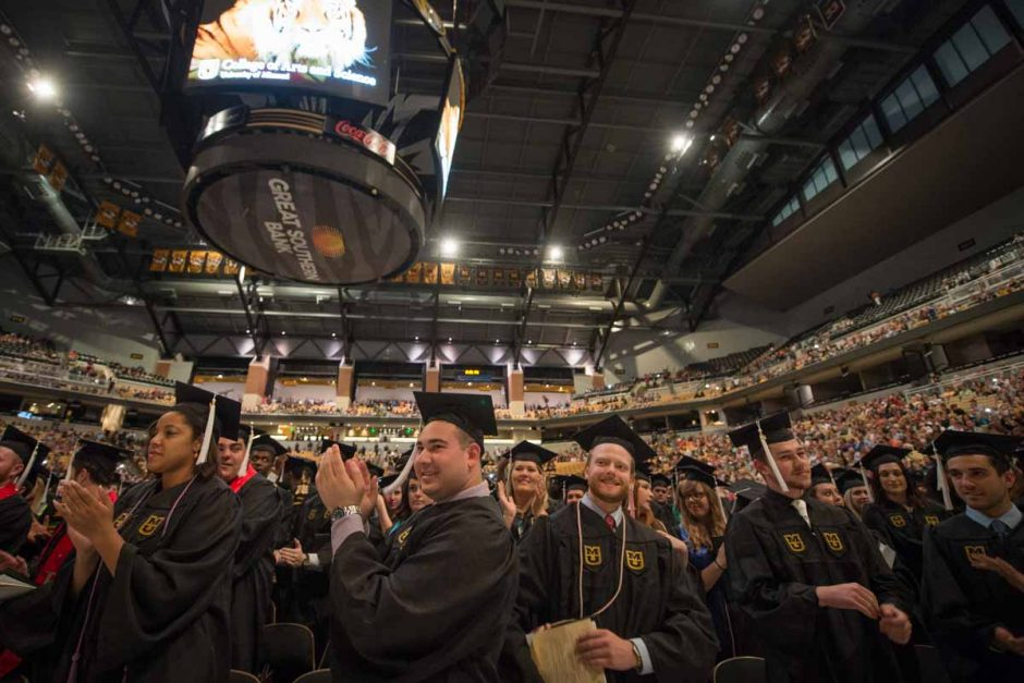 Students stand and applaud for one another at the end of graduation ceremonies. Photo by Shane Epping.