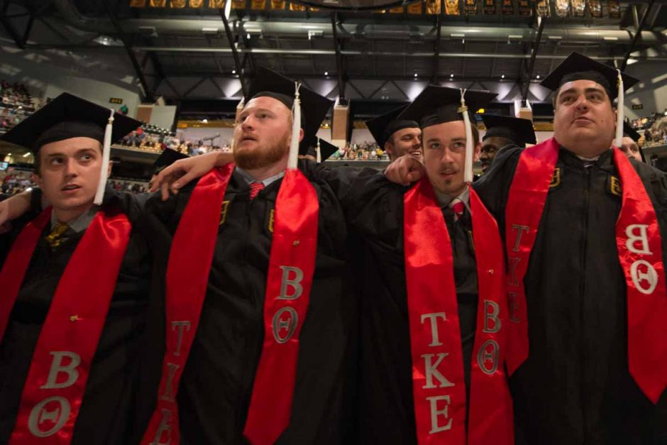 """Members of Tau Kappa Epsilon fraternity embrace one another while swaying and singing """"Old Missouri."""" Photo by Shane Epping."""