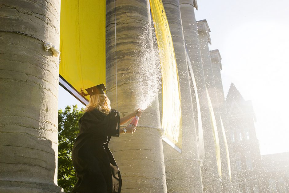 Taylor Gross, a 2016 textile and apparel management graduate from Sycamore, IL, sprays sparkling grape juice from the base of the columns.