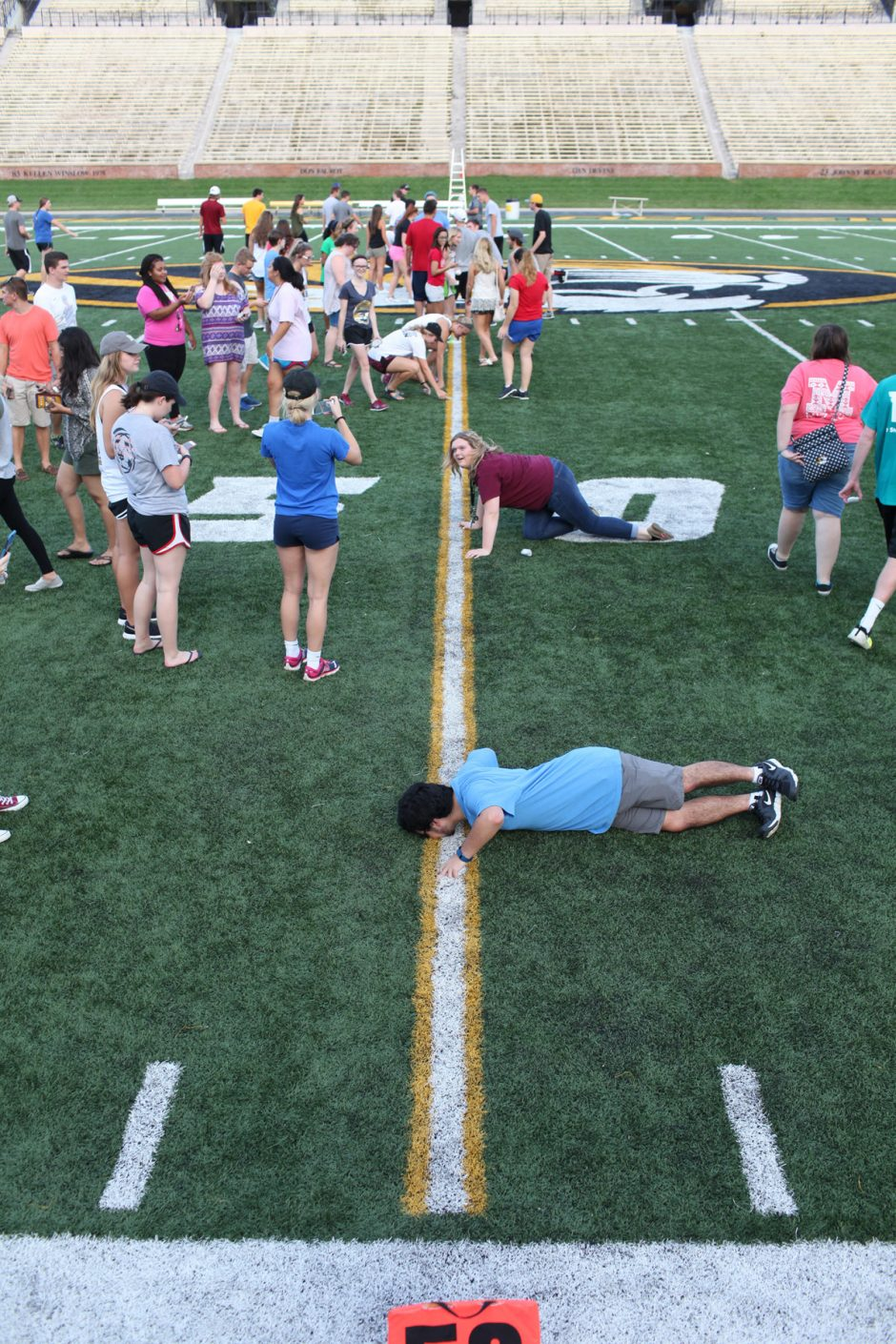 Students kissing the yard line.