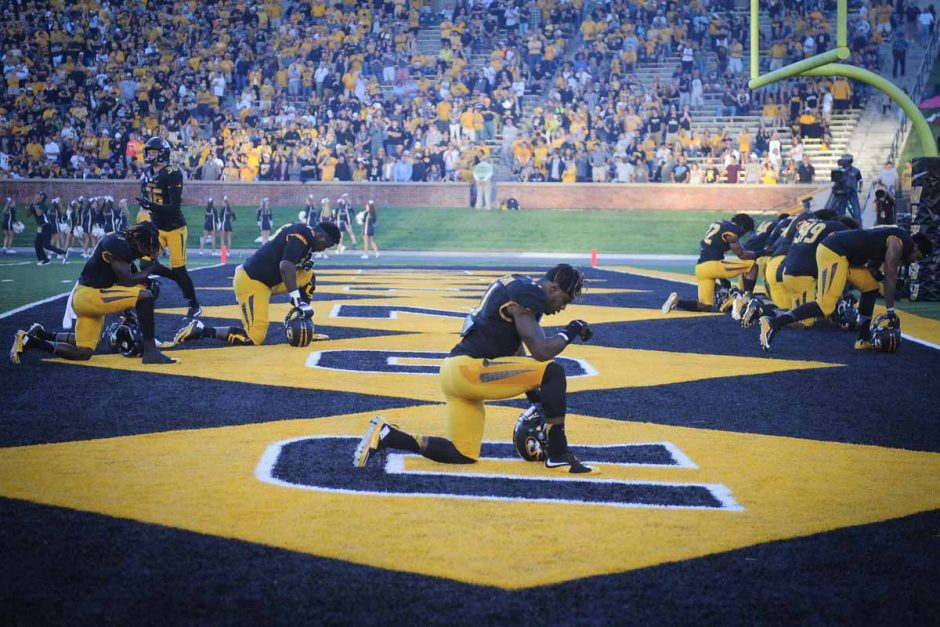 Players drop to a knee in the north end zone before the game begins.