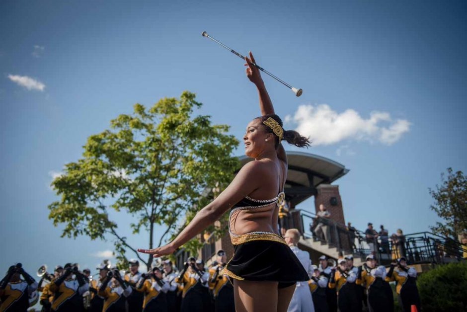 Freshman Simone Esters performs outside of Memorial Stadium during tailgating activities. Esters is the newest feature twirler for Marching Mizzou.