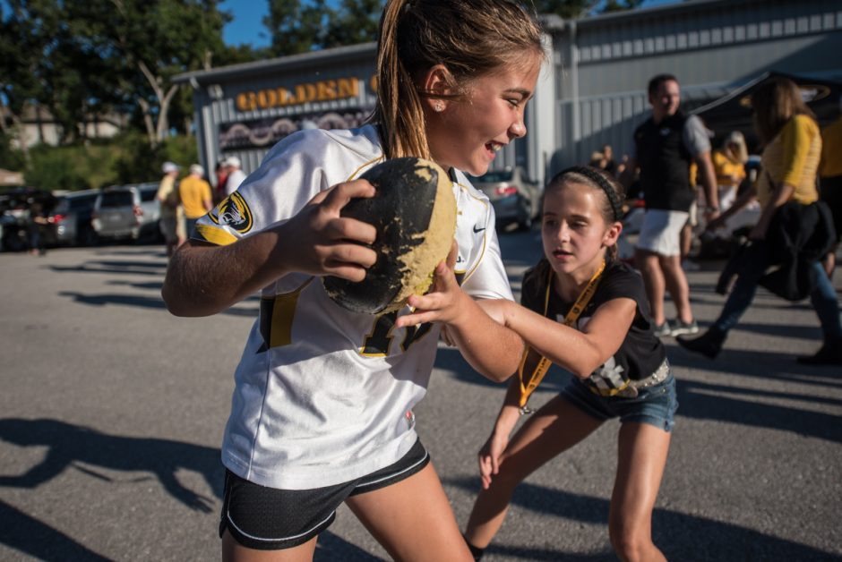 Ava Hughes, 9, plays against Sydney Schulte,9, in tailgating territory on Saturday.