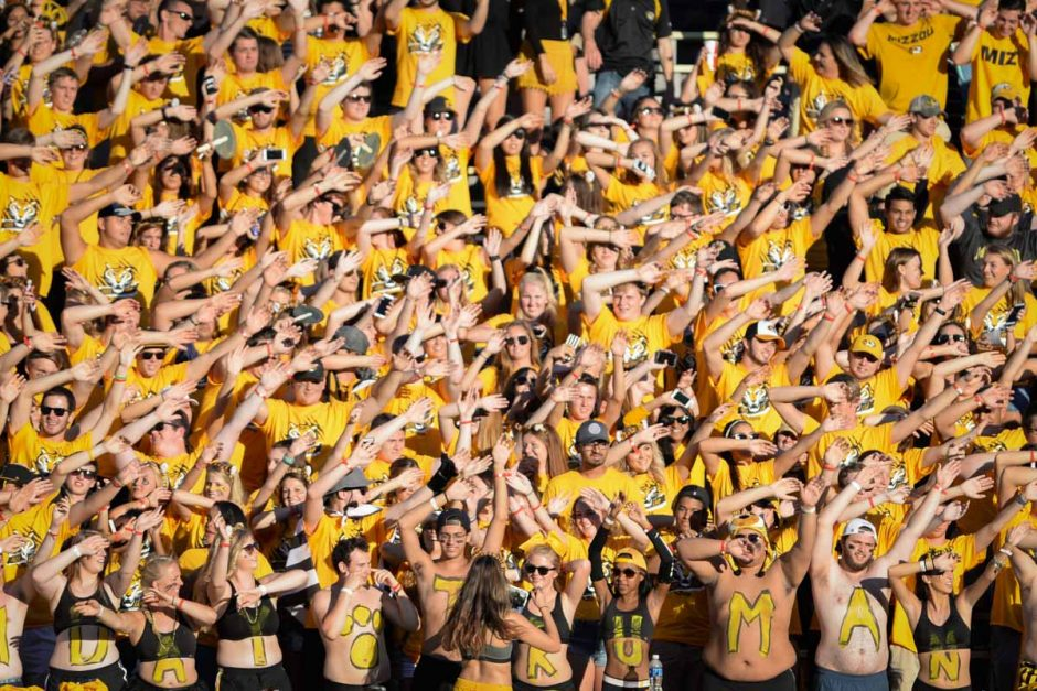 Fans in the student section on the east side of Memorial Stadium soak up the sun's fading rays before the game begins.