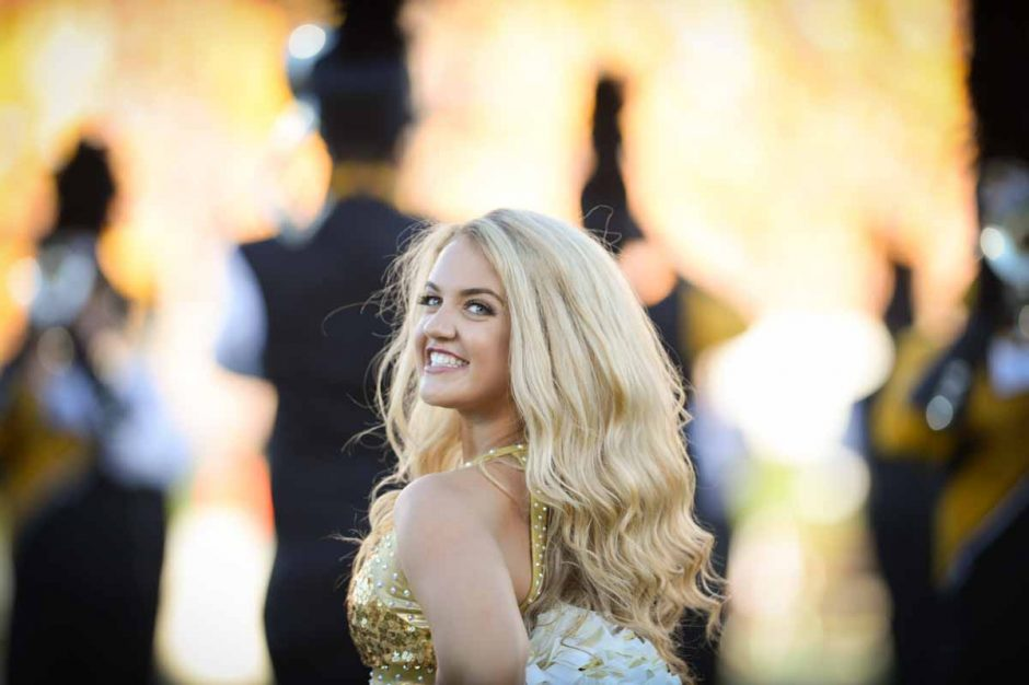 Golden Girl Ally Hill performs before the game begins on Saturday night.