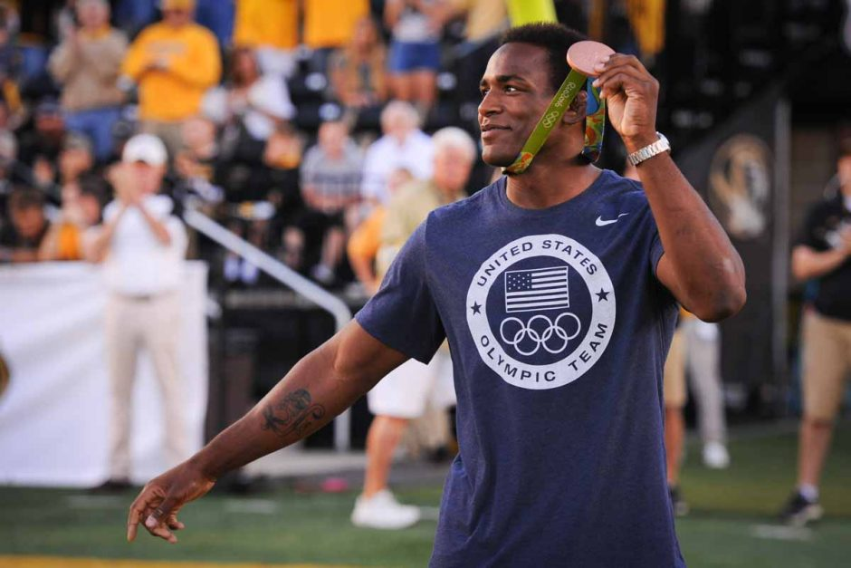 Mizzou senior J'den Cox shows off his Olympic bronze wrestling medal to the crowd after being introduced in the south endzone during a media timeout.