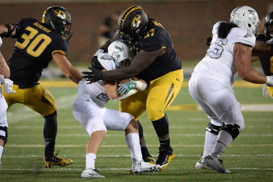 Senior defensive lineman Josh Augusta engulfs an Eastern Michigan player at the line of scrimmage.