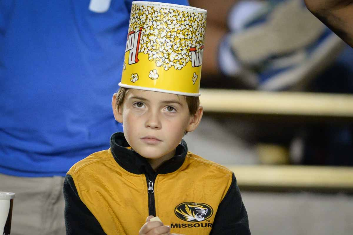 Jack Callahan, 10, keeps warm as temperature drop with a Univ of Missouri jacket and and empty bucket of popcorn.