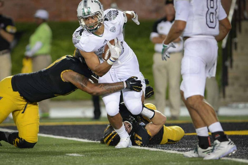 Freshman linebacker Cale Garrett holds on to Eastern Michigan's quarterback and stops him at the one yard line.