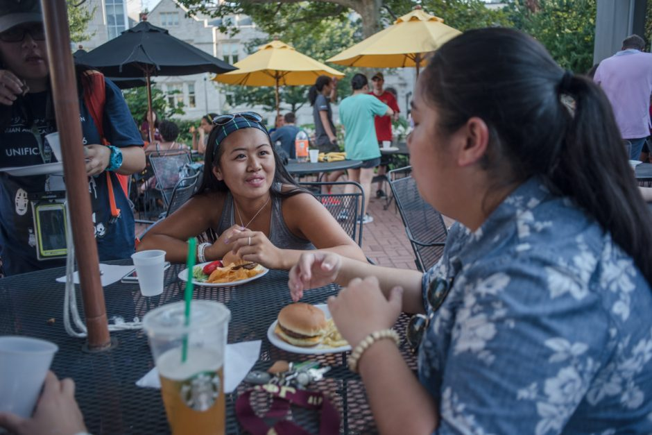 Two young women talking while eating burgers.