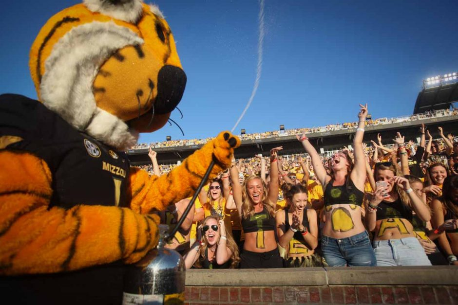 Tiger fans cheer as Truman the Tiger sprays water over the crowd before kickoff.