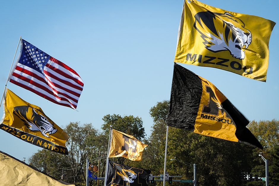 Mizzou and Ol' Glory flags fly high on the north side of Stadium Boulevard where tailgaters populate a parking lot. Photo by Shane Epping.