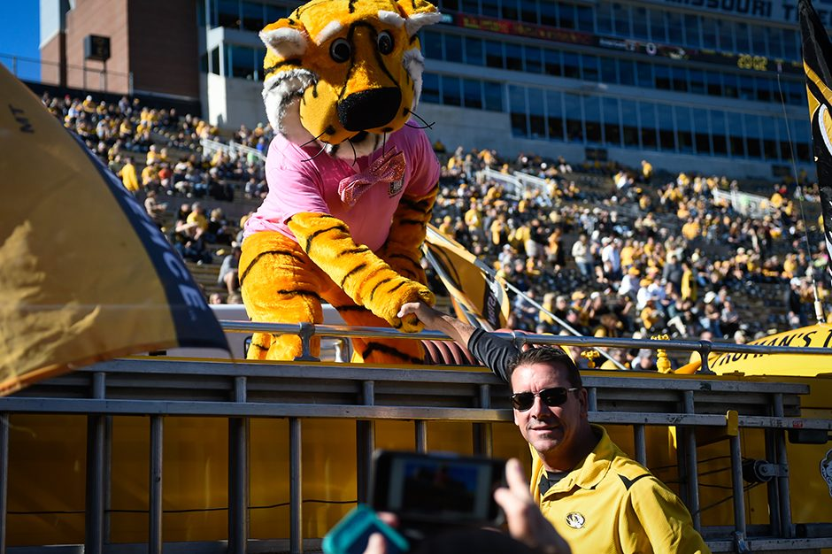 Truman shakes hands with a fan who poses for a cell phone picture on Faurot Field. Photo by Shane Epping.