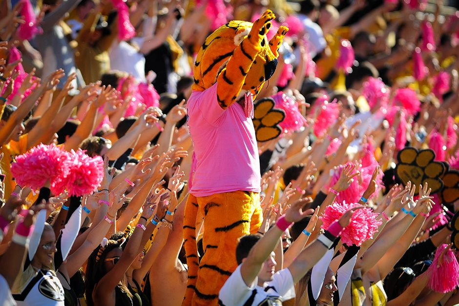Truman and members of Tiger's Lair raise their arms during the opening kickoff. Photo by Shane Epping.