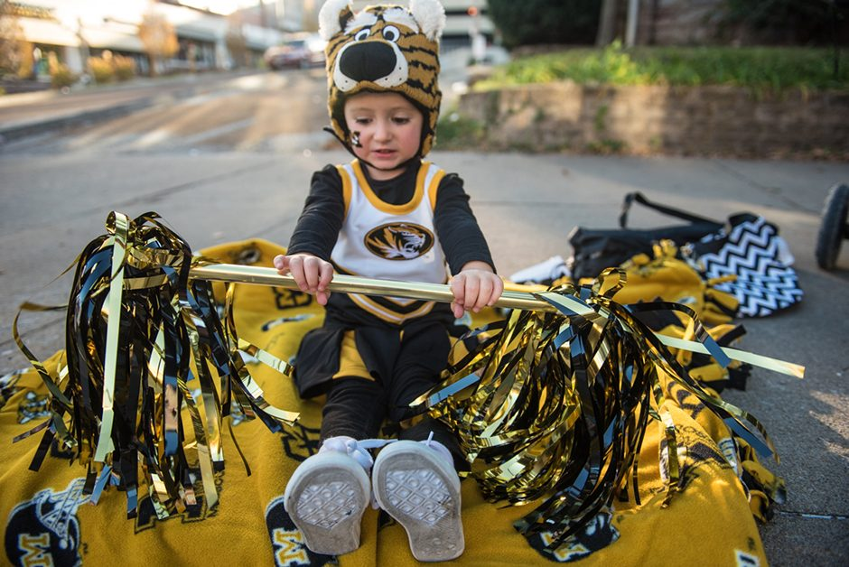 Little girl in a cheerleading uniform and a tiger hat, holding pompons.