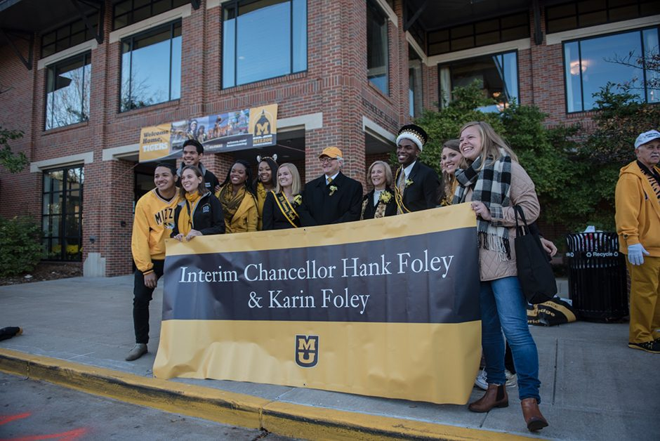 Students pose with the chancellor and his wife behind a banner.