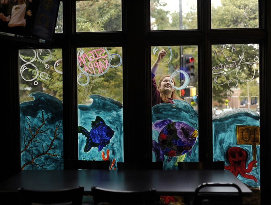 Sigma Kappa Sorority member Emily Chu paints the window painting outside of Campus Bar and Grill for decorate the distrcit on Thursday, Oct. 20, 2016. Sigma Kappa's theme was Rainbow Fish.