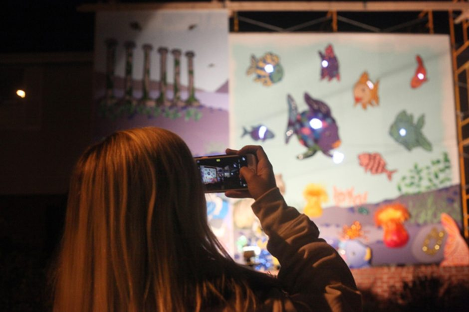 A woman takes a photo of the house decorations created by Sigma Kappa and Sigma Alpha Epsilon during the homecoming house decoration showcase on Friday, Oct. 22, 2016.